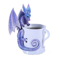 Guests will do a double-take if they see this mug sitting on your coffee table! The statue features a little dragon perched upon the side of the coffee mug, peering in. The drake is done in shades of blue and purple, with jewel-like indigo eyes. A unique figurine, and perfect for any dragon lover!