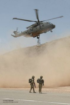 Soldiers watch as a Royal Air Force Merlin helicopter takes off with an underslung load in Afghanistan.