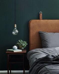 Masculine bedroom: Deep dark green walls, caramel leather headboard, grey bedding
