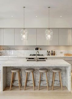Beautiful soft tones of white, bone, honey and pale stone in this contemporary London home … especially love the kitchen with its wide-planked wood floors, striking marble island and counters, plus th