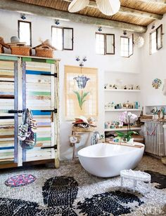 Bohemian inspired bathroom with stone floors, wood ceilings, and a large tub!