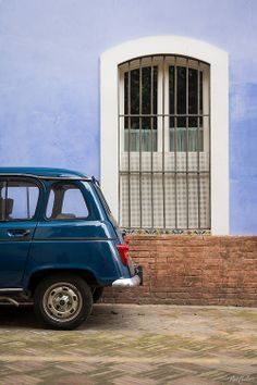 A teal Renault car sits parked in front of a pale blue, stucco wall and shuttered window in the heart of the Judería quarter in Seville, Spain. Prints available; for details visit www.NatCoalson.com