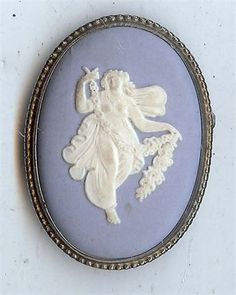 On offer is this classic brooch / pin from the English china company Wedgwood .   An oval jasperware cameo design set in hallmarked sterling silver .   A fair maiden to center with flower garland .   A vintage piece - not new .   Needs a quick clean , great condition .