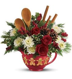 They'll bake merry with this bright holiday mixing bowl ringed with enchanting gingerbread people. In addition to colorful flowers, the arrangement features wooden baking spoons, which leads us to the savory sweepstakes described below. They'll eat it up.    The cheerful bouquet includes red roses, white cushion spray chrysanthemums, noble fir, flat cedar, white pine and variegated holly and pinecones - topped off with wooden mixing spoons.