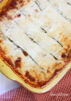"Zucchini Lasagna | Skinnytaste1 lb 93% lean beef 3 cloves garlic 1/2 onion 1 tsp olive oil salt and pepper 28 oz can crushed tomatoes 2 tbsp chopped fresh basil 3 medium zucchini, sliced 1/8"" thick 15 oz part-skim ricotta 16 oz part-skin mozzarella cheese, shredded (Sargento) 1/4 cup Parmigiano Reggiano 1 large egg"