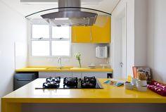 Cozinha cinza e amarela Bancada e Ilha com pedra amarela e marcenaria cinza com armário superior de vidro amarelo. Revestimento de pastilha hexagonal no frontão.