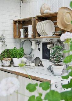 Une cuisine pleine de charme avec des étagères faites de caisses en bois.