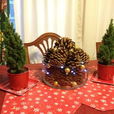 Christmas table... Pinecones with small gold balls and LED lights along with the small trees make a simple festive every day holiday table.