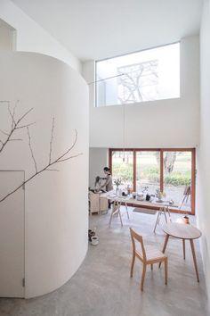 階段前から見る。左の、キッチンなどの入る楕円形スペースの上はバルコニーで、上の窓を通して公園の風景を眺められる。