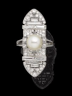 A cultured pearl and diamond dress ring Of geometric design, the navette plaque, set throughout with graduated single and baguette-cut diamonds, and to the centre with an 8.9mm cultured pearl, diamonds approx. 2.20cts total. Art Deco or Art Deco style.