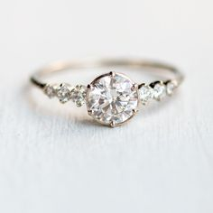 This is it. This is my favorite ring of all time. Low profile, silver, circle cut, thin band with accent diamonds in the side. Made by a local company. Absolute perfection. Diamond Cadence Ring #DazzlingDiamondEngagementRings