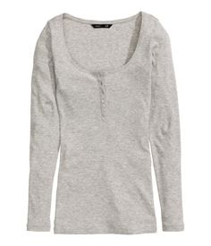 White. Fitted top in soft cotton jersey with a scoop neckline, buttons at front, and long sleeves.