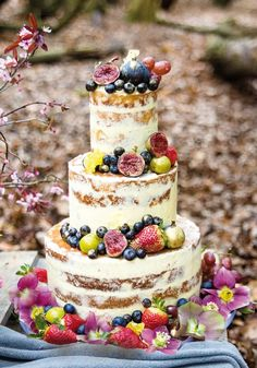 Boho brides, you are going to LOVE this rustic semi naked cake - it looks so beautiful decorated with fresh fruit and flowers around the base, with delicious vanilla frostings temptingly oozing out of each layer... YUM! We Go Around The World In 8 Wedding Cakes To Find The Best Ideas For You! See them all on the Wedding Ideas website!