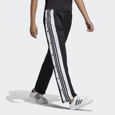 Recognizable 3-Stripes down the sides of these women's track pants keep the modern look pulsing with adidas heritage. Bringing back an iconic style, the shiny tricot design references the '90s Adibreak breakaway pants with snap buttons that run from the waist to the cuffs. They come in a relaxed fit with a wide leg. adidas is dedicated to creating products in ways that minimize their environmental impact. These pants are made with recycled polyester to save resources and decrease emi...