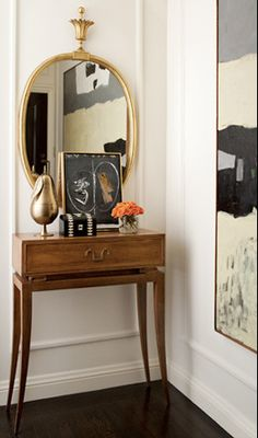 Small with big design - sculpted gold pear, prints, elegant hall table with fine detailing plus a Tommi Parzinger mirror for reflections.