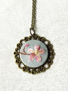 Marg Dier Embroidery. Hand embroidery cherry blossom necklace pink with blue silk. Thread painting art embroidery. A single flower of cherry blossom has been