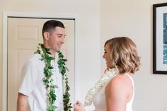 Bride and groom getting ready together before their vow renewal wearing wedding leis