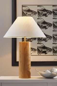 Liven up your living space with the Martin Table Lamp. Crafted of natural oak wood with a touch of antique brass metal, this lamp will add a classy touch of modern styling to your home. A retro-inspired shade shape is comprised of white textured fabric.
