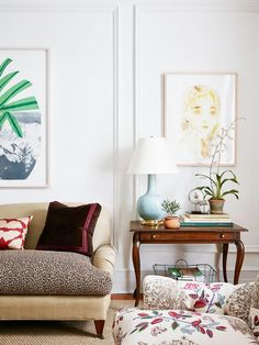 A neutral sofa with velvet pillows and bold, colorful art on walls in living room // Lauren McGrath's New York apartment