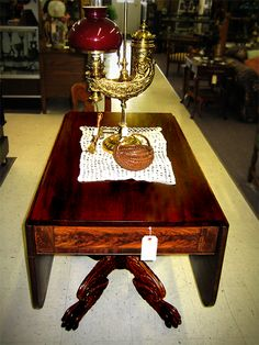 "This ""paw foot"" table is a striking example of Victorian furniture. The legs showcase unusually fine carving and the top and sides are all single boards. Made of walnut and mahogany. On top of the table is one of our Harvard student lamps.  #interiordesign #forsale #furniture #robertsantiques #antiques #homedecor #design #antiquefurniture #pawfoot #apartmenttherapy #decorating #southernliving #antique #victorian #woodwork #mahogany #walnut"