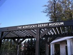 This photographic image is of a sign for the Kentucky Derby Museum over a walkway nearby the museum. Find this image and more for sale at marian-bell.pixels.com marian-bell.fineartamerica.com More items available at zazzle.com/marianbellbellaspix*