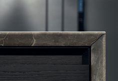 Particolare del top in pietra Stone brown levigato e delle ante in rovere spessart della cucina Trail di Varenna Poliform
