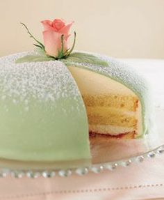 A princess cake (prinsesstårta in Swedish) is a traditional Swedish layer cake consisting of alternating layers of airy sponge cake, pastry cream, and a thick-domed layer of whipped cream. This is topped by marzipan, giving the cake a smooth rounded top. The marzipan overlay is usually green, sprinkled with powdered sugar, and often decorated with a pink marzipan rose.