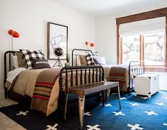 Another shot of this fun kids bedroom! Wanted to show you how we chose 2 different beds and 2 different benches but used other elements like the bedding, the sconces, the rug and the custom art to pull the room together! #schoolhouseliving