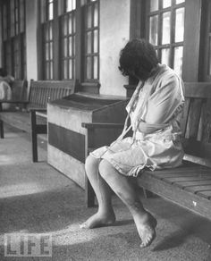 A female patient, who is restrained in a straightjacket, sits alone on a bench and cries in a mental institution, Youngstown, Ohio, 1946. There are open, untreated sores on her leg.