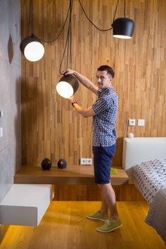 The bright glow of the FLOS AIM pendant lights illuminates this modern interior with wood walls and a wood floor.