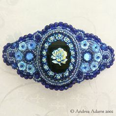 Blue Rose bead-embroidered barrette centers around a vintage West German glass cabochon with a peacock blue rose design on a black base. Surrounded with soft blue ab seed beads, and accented with vintage Swarovski crystal flatbacks in sapphire blue.