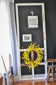 Who says a screen door has to function as a door? Blogger Holly repurposed it with chicken wire, then added a wreath and pictures to turn it into a shabby chic display.