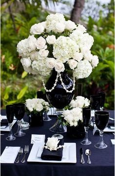 black vases, white flowers. A very pretty floral setting for a wedding or could be used as a centerpiece at a formal gathering, like a prom or banquet.