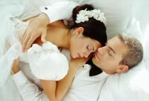 Bride and groom sleeping in embrace, elevated view - Nancy Brown/Photographer's Choice/Getty Images