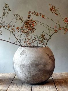 beautiful simplistic arrangement of red berries in a stone (?) pot