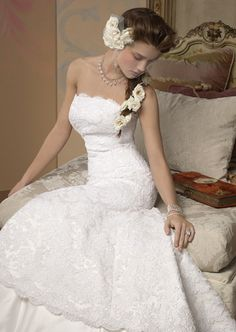 Pretty lace dress. The way she has the Flowers going through her hair takes the place of not wearing a veil.