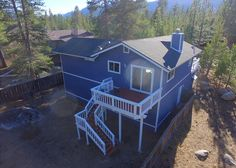 Backyard overhead view of the home, fully-fenced yard, deck with BBQ (not pictured), table and chairs  #drone #overview #cabin