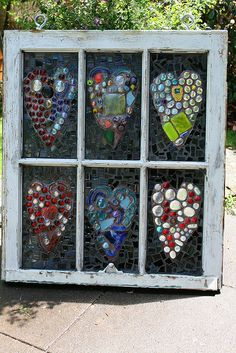 I want to make one of these to hang in my classroom window at the  high school! Recycled window filled with mosaic hearts. Would be beautiful in the sun!