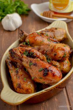 delicious golden sticky honey garlic chicken in dish with honey, garlic and herbs in background