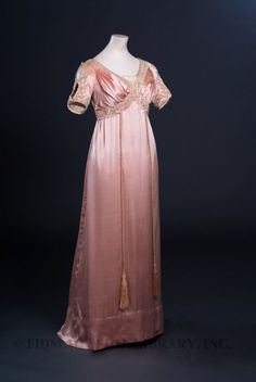Evening gownLiberty & Co.c. 1910Silk satin, silk gauze & pearl beads Liberty & Co. opened in Londons West End during 1875. Founder Arthur Lasenby Liberty stocked his small shop with goods imported from the Middle East and Japan, including curios, porcelain, fans and lengths of fabric. Libertys shop had a bazaar-like atmosphere and attracted a clientele sympathetic to the ideals of the Aesthetic Movement. From the beginning, textiles were an important part of ...