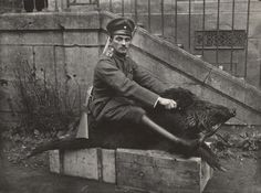 A German Air Force officer sits astride a dead boar outside a house where he is stationed near the Western Front in 1918
