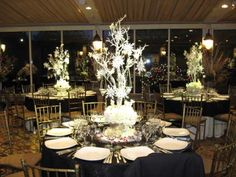 branches potted and painted white with snowflake ornaments and hung candles dangling - Navy table cloths