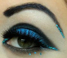 Blue crystals enhance dramatic blue and black eye shadow with a bejeweled black brow by MUA Krissii.
