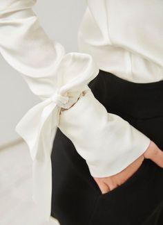 Blusa de seda con un delicado y especial acabado brillo, propio de tejidos de gran calidad. Corte recto, escote cascada y manga larga con triple ojal de botones detallado por un maxi lazo.