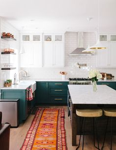 In this kitchen, deep teal-green cabinets are grounded by a vintage Guatemalan rug. | Photographer: Becky Kimball | Designer: Ali Hynek