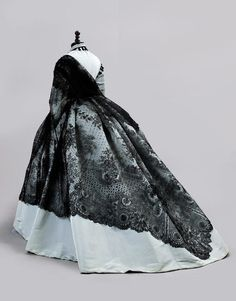 A BLACK CHANTILLY LACE SHAWL 1860s of square shape, with floral sprays above a lattice border