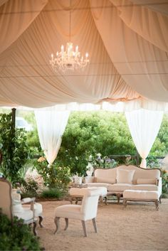 I LIVE for this white draped silk with chandelier, safari-style!