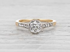 Antique late Edwardian engagement ring made in platinum and 18k yellow gold. Centered with an approximately 1.05 carat EGL certified old European cut diamond with F-G color and SI2 clarity and accented with single cut diamonds. Circa 1915.
