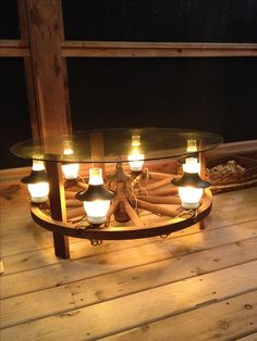a coffee table made from a wagon wheel chandelier add three wooden legs and a glass top and it becomes the perfect lighted accessory and conversation piece alternating length wagon wheel mason jar