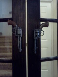 My husband found metal toy guns on the internet and glued them on door handles for his man cave.